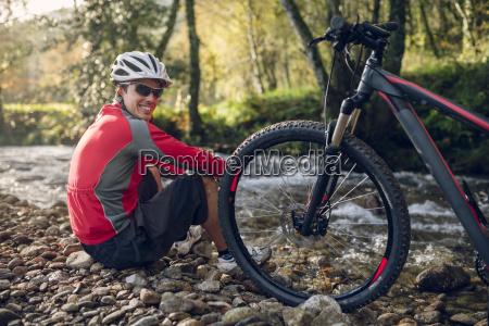 mountain biker sitting at river