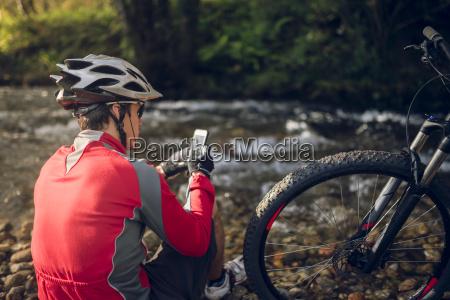 mountain biker sitting at river using