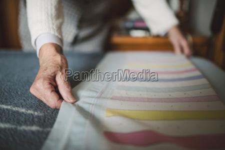 senior woman putting fresh sheets on