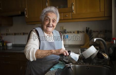 senior woman washing dishes in kitchen
