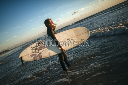 woman with surfboard dressed in wetsuit