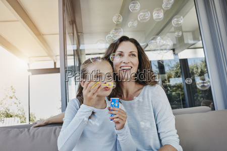 mother and daughter blowing soap bubbles
