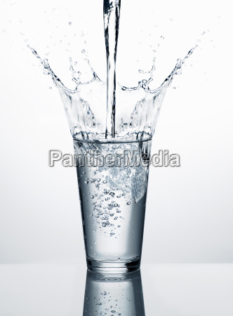 pouring water into glass in front