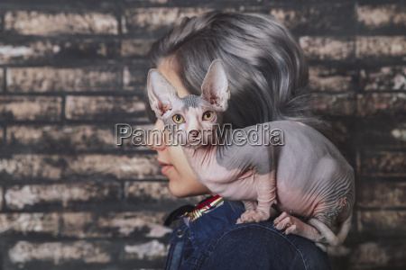young woman carrying sphynx cat on