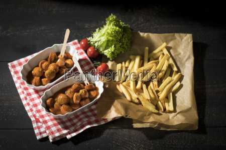 two bowls of currywurst and french