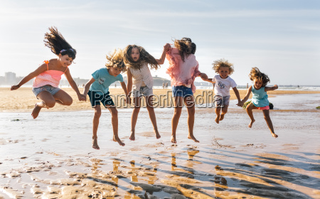 group of six children jumping in