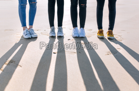 legs of four friends standing side