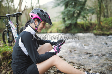 smiling woman with mountain bike resting