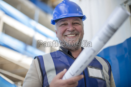 engineer on construction site holding blueprint