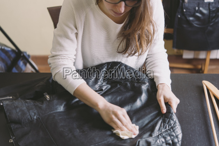 woman cleaning leather jacket