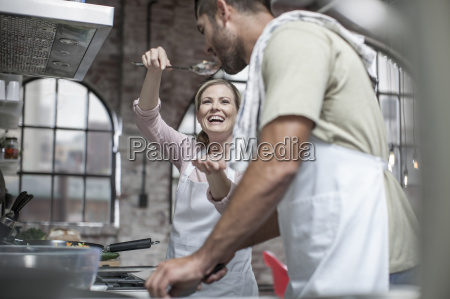 happy couple cooking together in kitchen