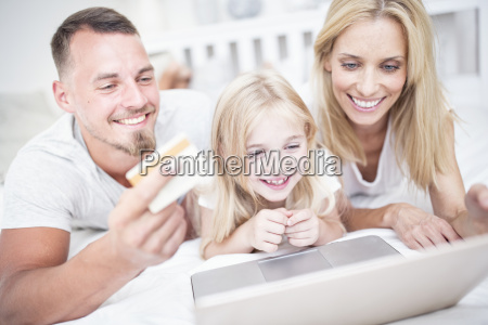smiling girl with parents lying in