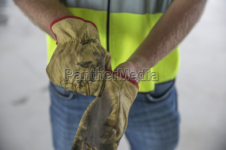 construction worker putting on protective gloves