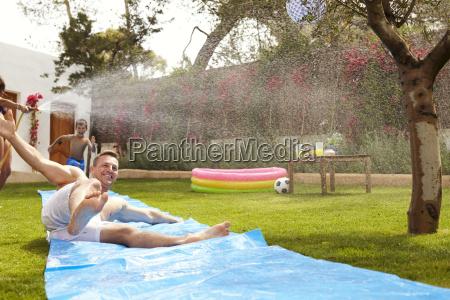 family having fun on water slide