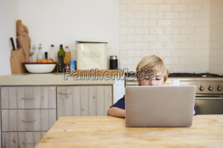young boy using laptop computer at