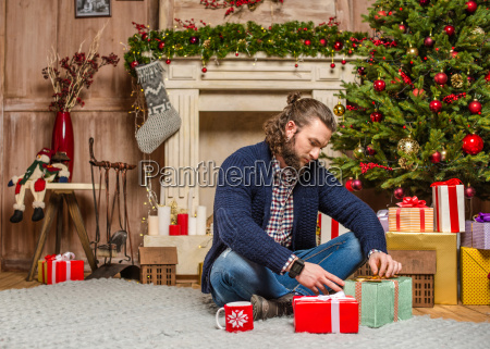 man sitting with christmas presents