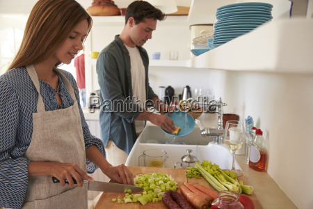 young adult couple preparing food