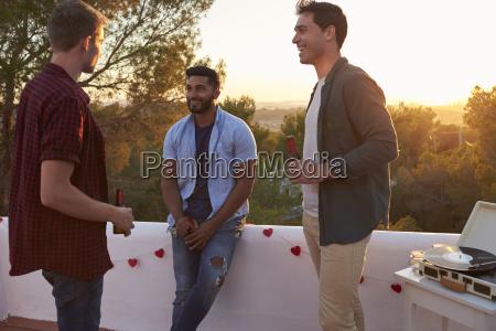 three male friends talk at a