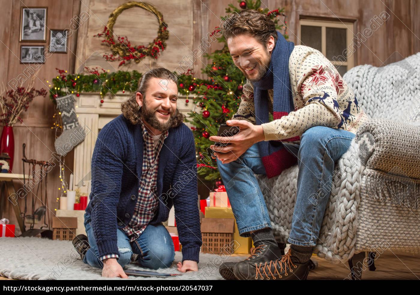 smiling, men, looking, at, smartphone - 20547037