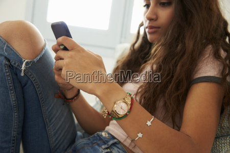 teenage girl text messaging with phone