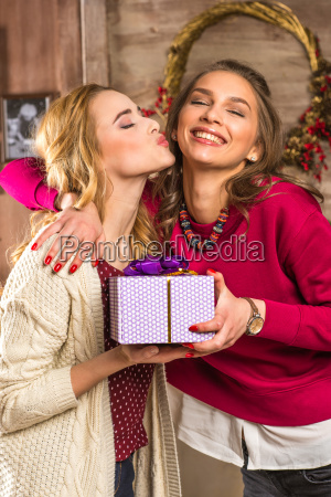 cheerful women holding gift box