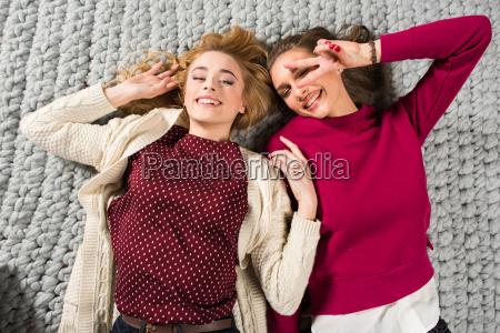 happy, women, lying, on, grey, carpet - 20548511
