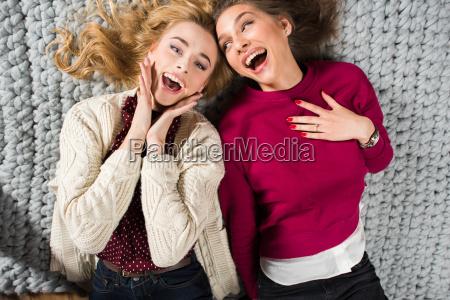 women, lying, on, grey, carpet - 20548513
