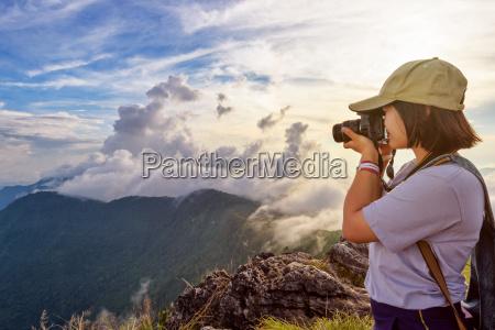 hiker taking photo at sunset