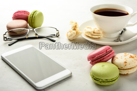 tea with macaroons smartphone and glasses