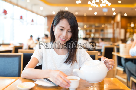woman, drinking, tea, in, chinese, restaurant - 20553341