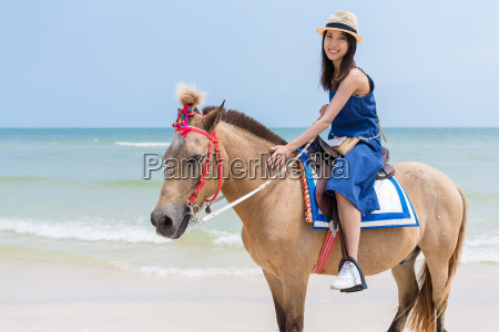 young woman riding horse in sand