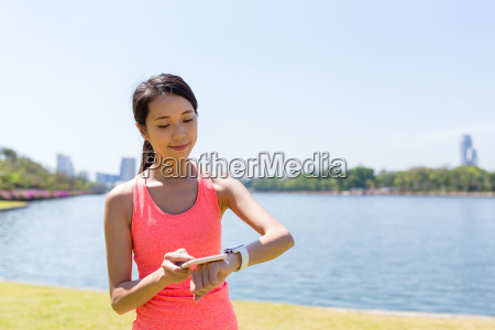 woman connecting cellphone and smart watch