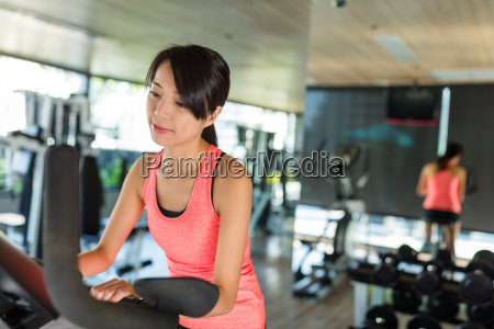 woman, cycling, bike, in, gym, room - 20557933