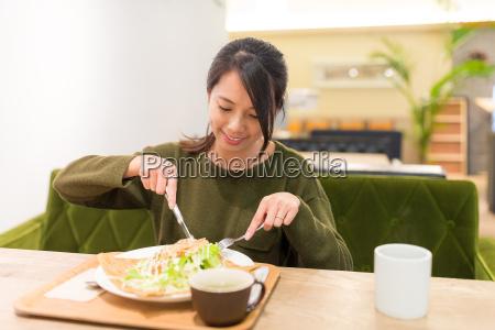 woman, having, pancake, in, restaurant - 20557891