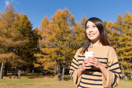 woman, holding, coffee, cup, at, autumn - 20557815