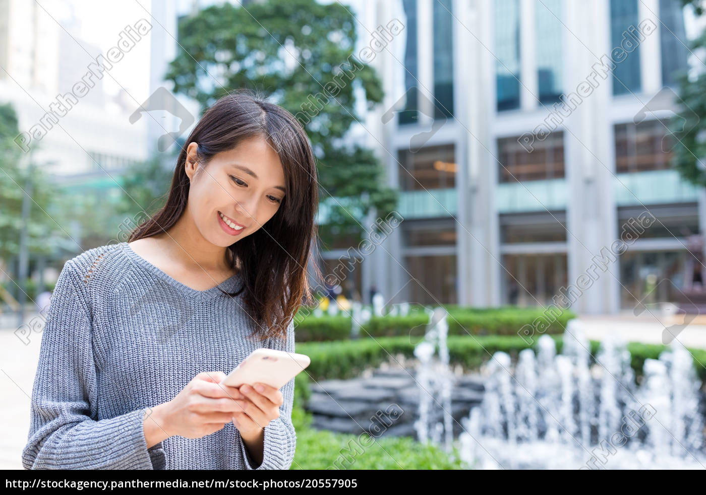 woman, sending, sms, on, mobile, phone - 20557905