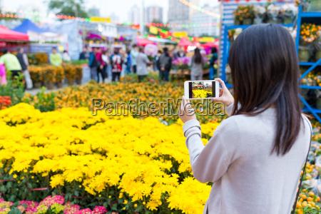 woman, taking, photo, on, flower, in - 20557919