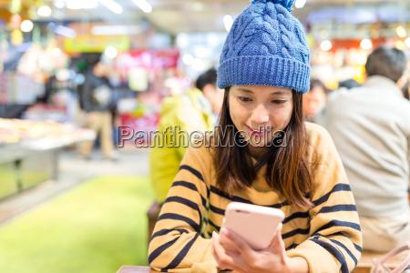 woman, using, cellphone, in, japanese, restaurant - 20557825