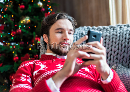 smiling, man, using, smartphone - 20558653