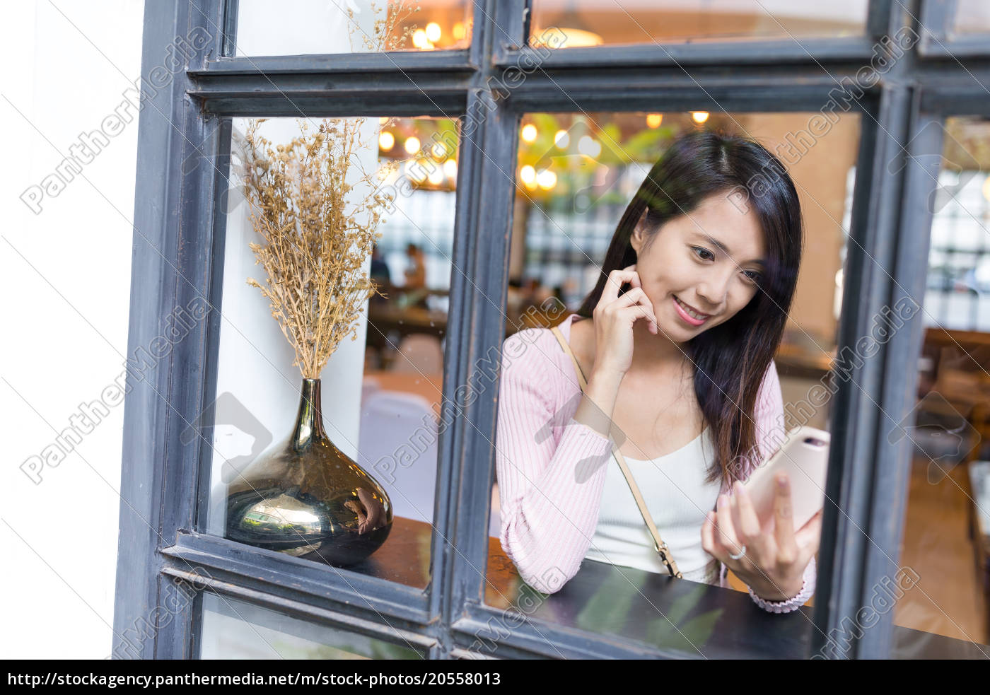 window, through, woman, use, of, mobile - 20558013