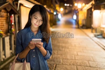 woman, sending, sms, on, cellphone - 20558947