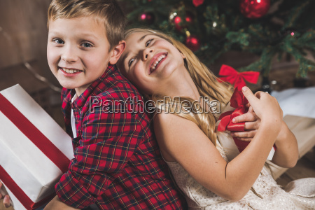 siblings holding gift boxes