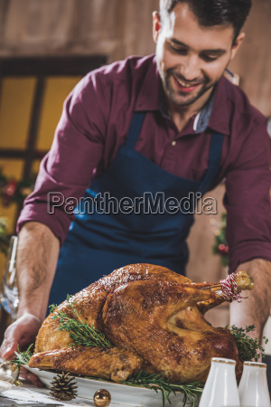 man, putting, turkey, on, festive, table - 20559353
