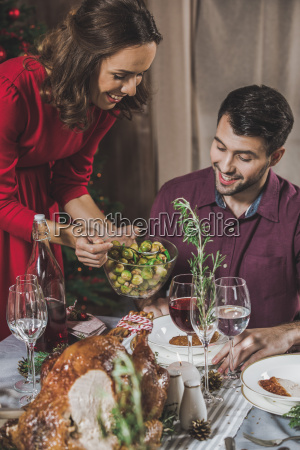 woman, putting, brussel, sprouts, on, plate - 20559381