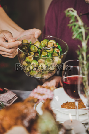 woman, putting, brussel, sprouts, on, plate - 20559383