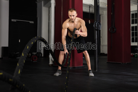 man using training ropes in a