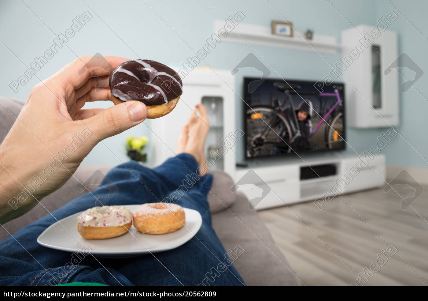 person, eating, donut, while, watching, television - 20562809