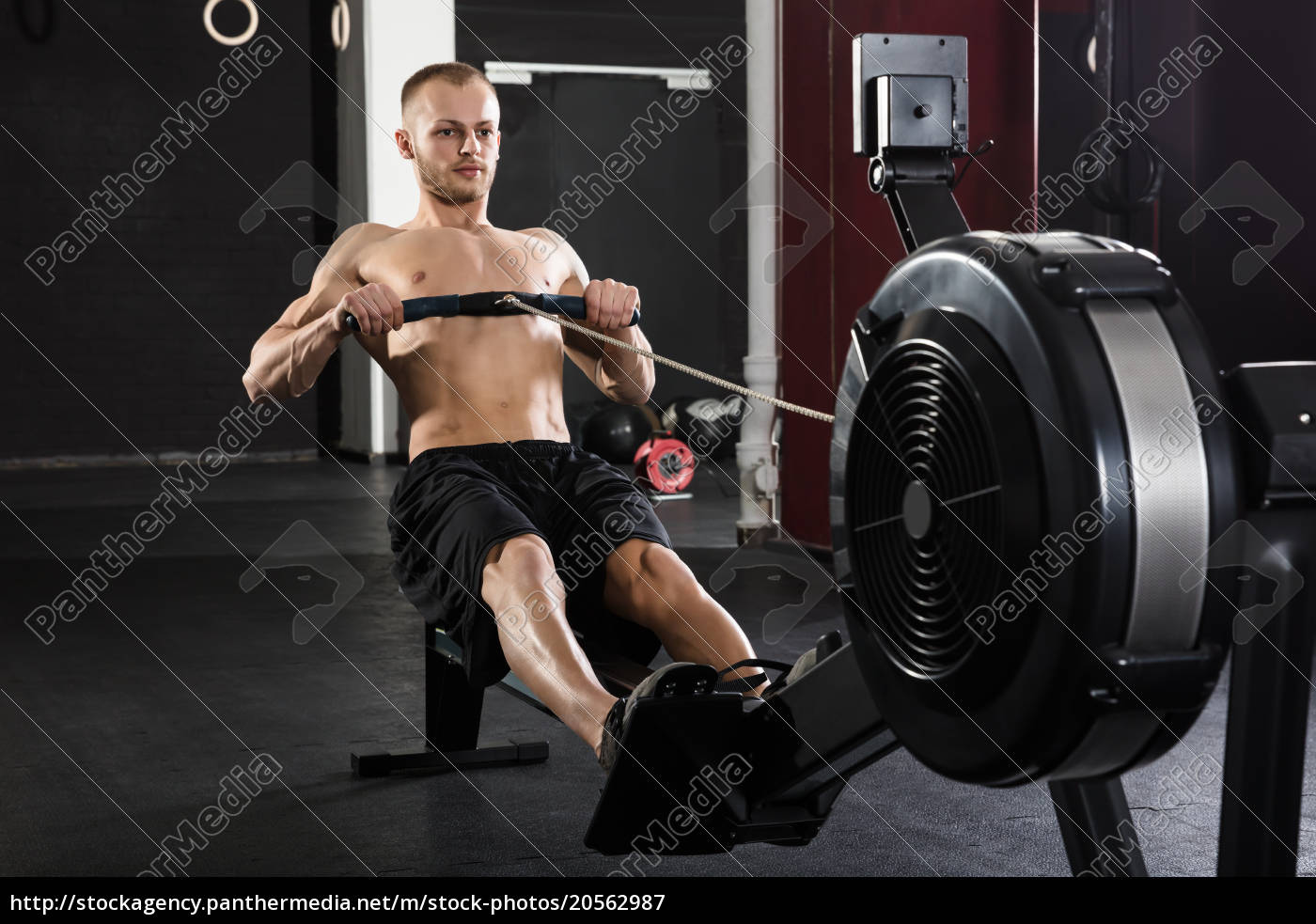 young, man, exercising, with, row, machine - 20562987