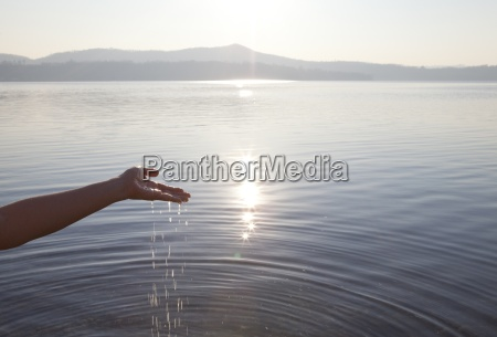 water pours from hands into tranquil