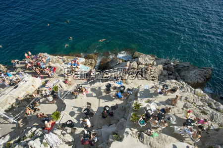 sunbathers and swimmers enjoy a recreation